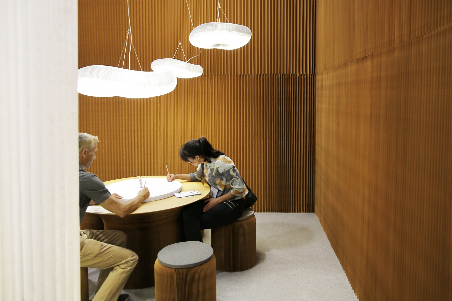 honeycomb paper furniture and cloud lighting by molo - guests at ICFF 2015 draw on molo's sketching circles accessory for cantilever table