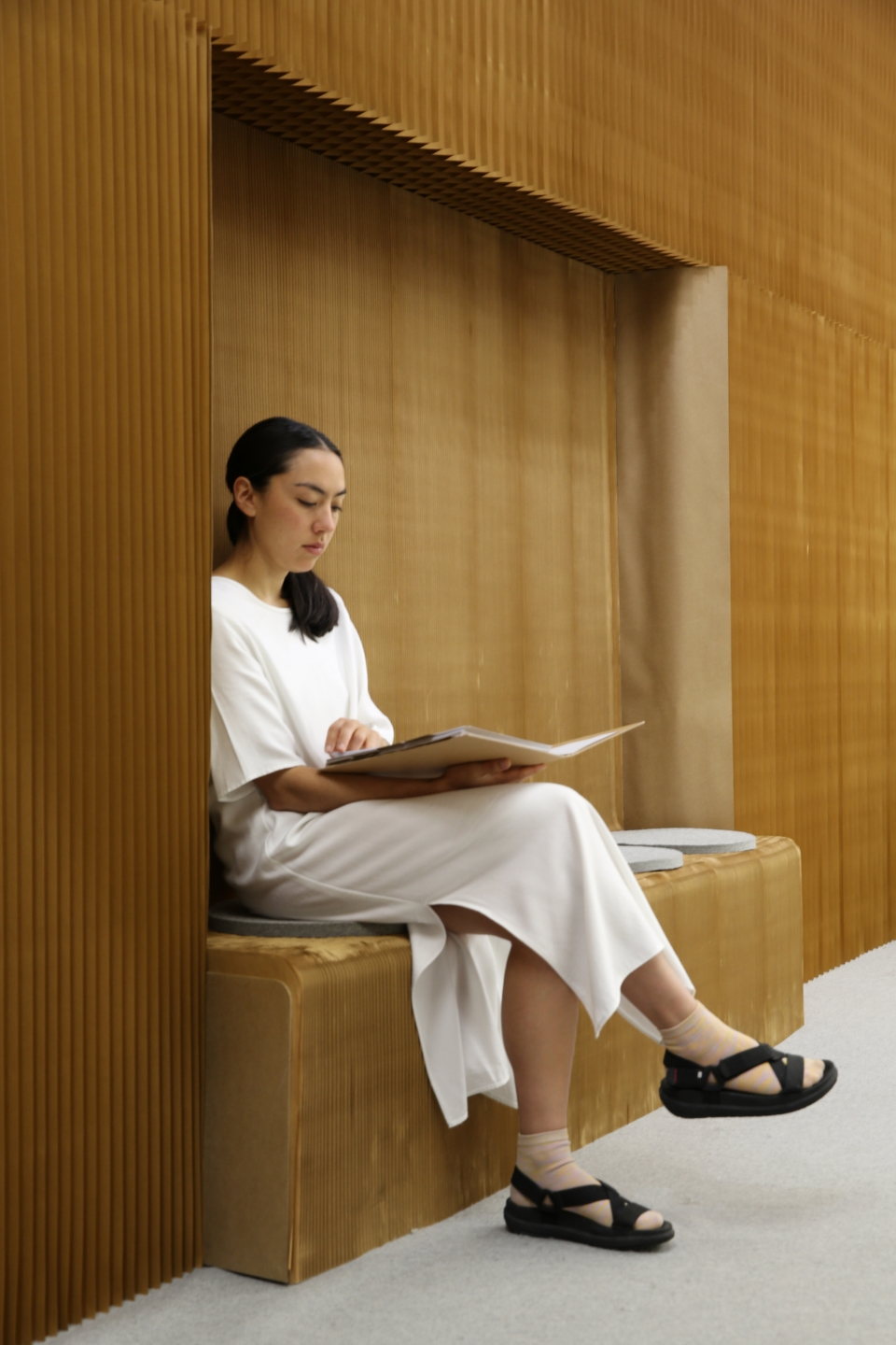 a woman sits and reads on a benchwall recessed into other softwalls