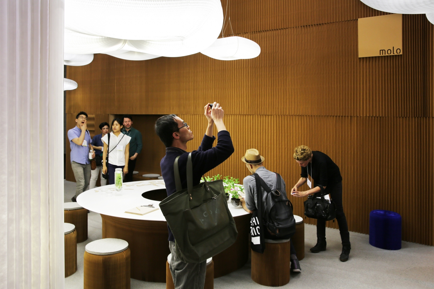 honeycomb paper furniture and cloud lighting by molo guests admire molo's installation at ICFF 2015