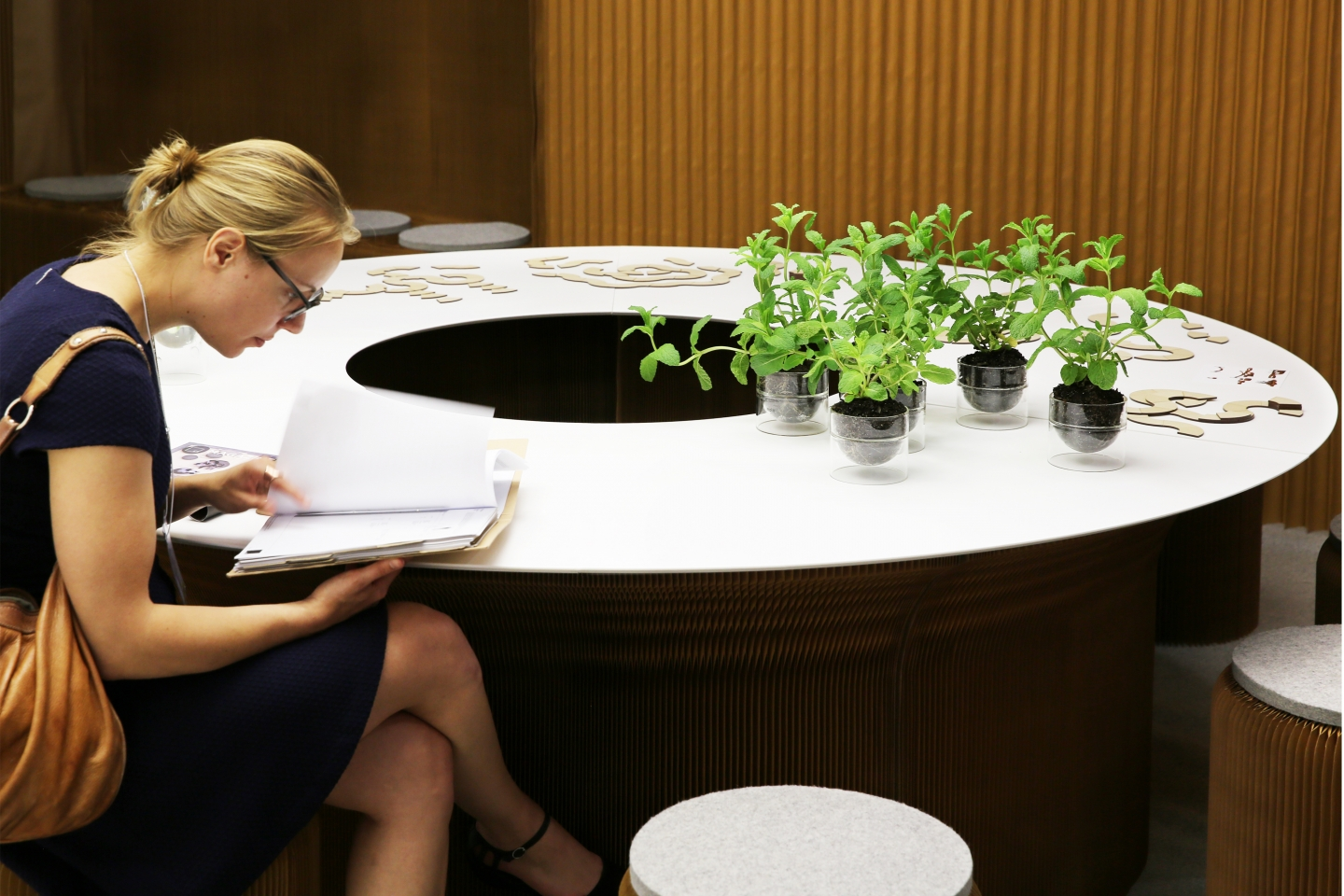 a woman reviews notes while sitting at a cantilever table with wedge tops.
