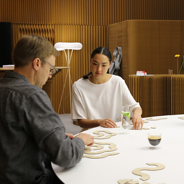 paper furniture inventors, molo, demonstrating possible arrangements for cantilever table with modular wedge tops
