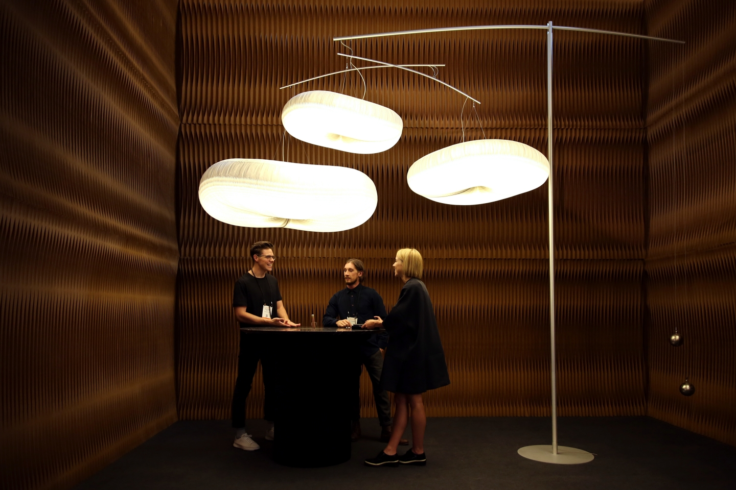 paper lighting and accordion paper furniture by molo - three people chat underneath cloud mast at ICFF 2016