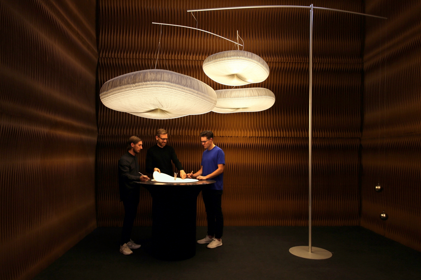 paper lighting and accordion paper furniture by molo - a group chats around a cantilever table with a black marble top, beneath a canopy of clouds