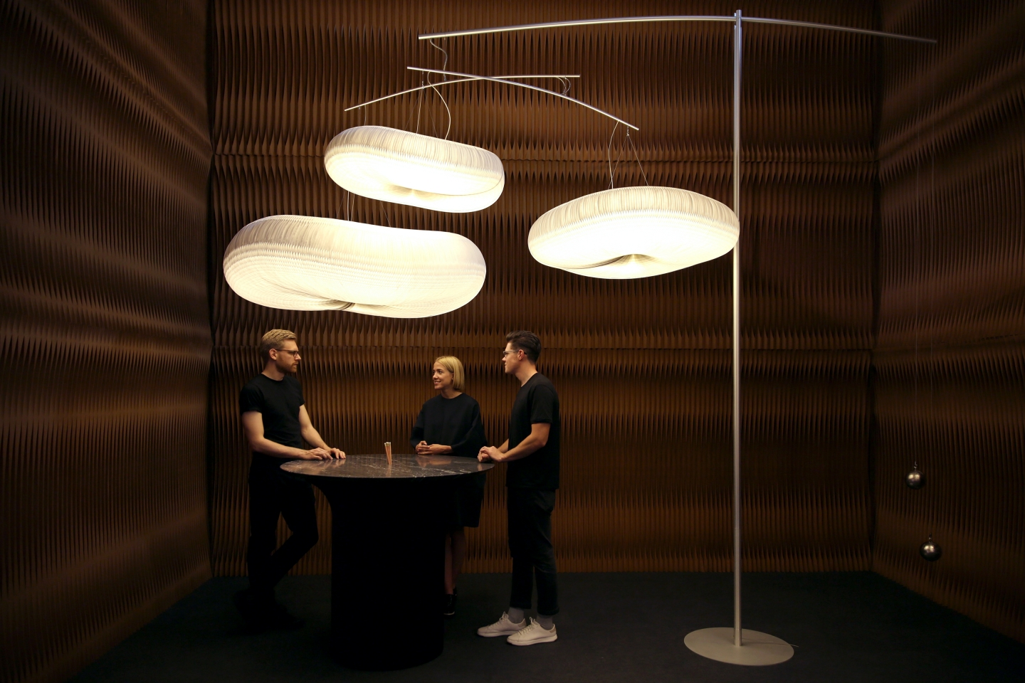 paper lighting - cloud mast by molo - three people chat below a large cloud mast at molo's ICFF 2016 installation