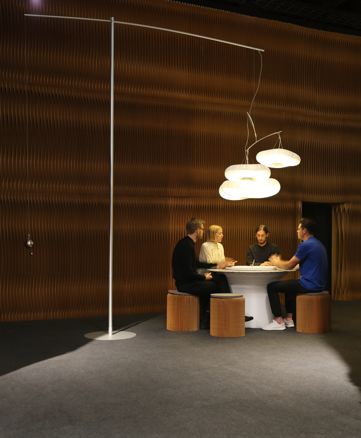 paper lighting and accordion paper seating by molo - a table of people chats animatedly below cloud mast