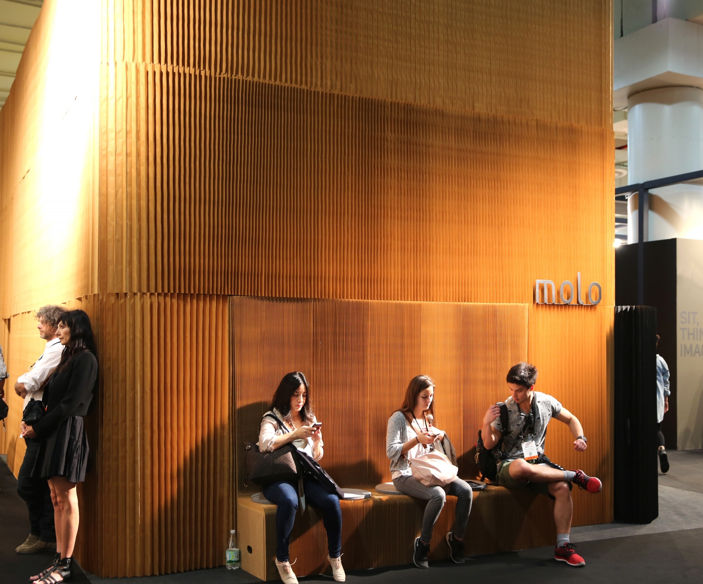 paper seating / accordion paper furniture by molo - guests take a rest on benchwall at molo's installation at ICFF 2016