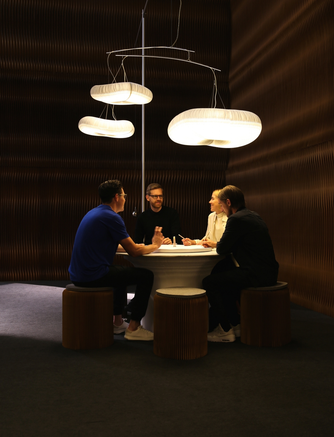 paper lighting and accordion paper furniture by molo - a table of people chats animatedly below cloud mast