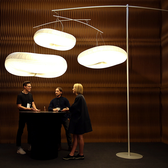 paper lighting and accordion paper furniture by molo - three people chat underneath a glowing canopy of clouds