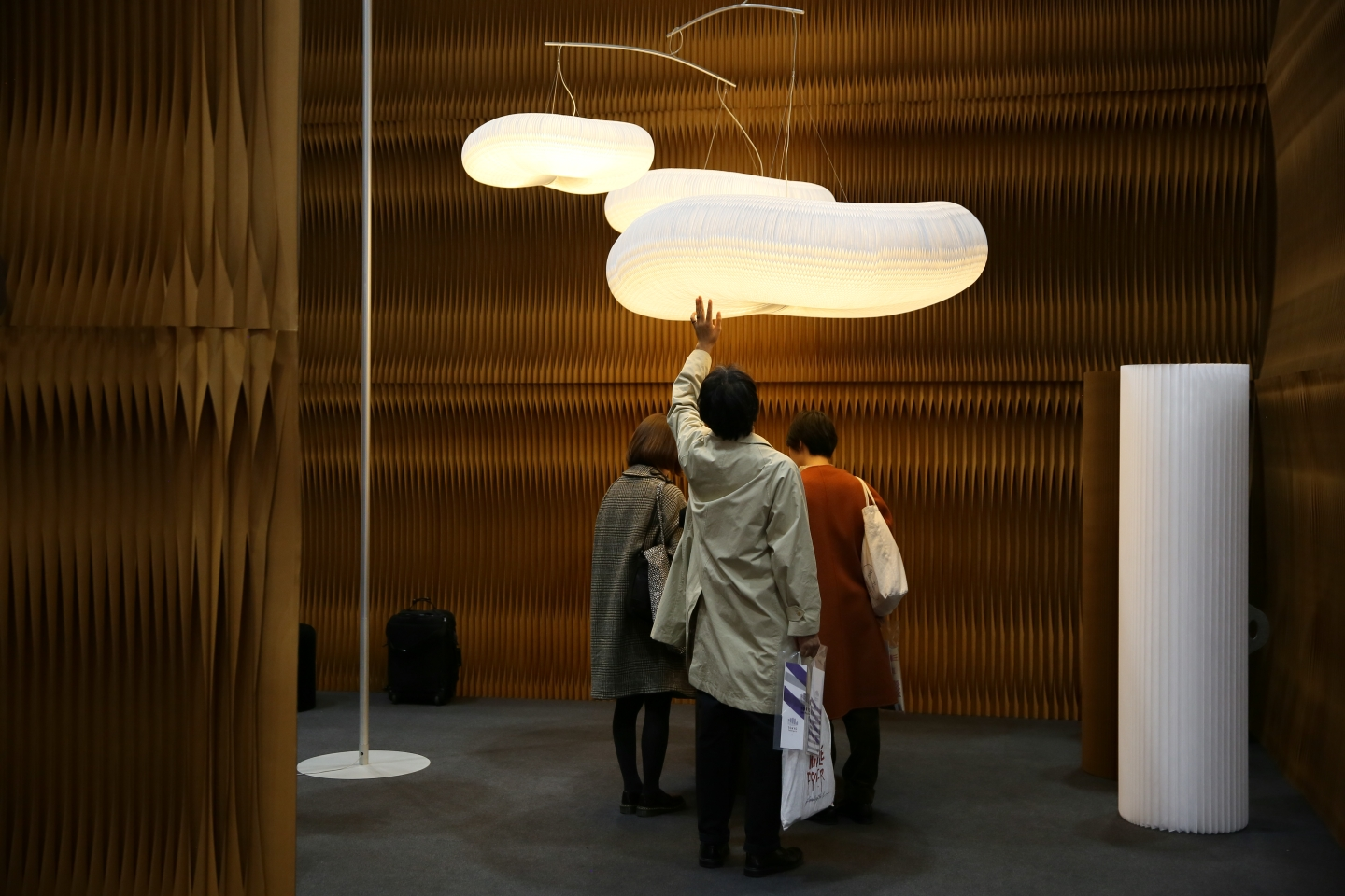 a man reaches to touch the textile honeycomb shades of cloud mast at IFFT in Tokyo
