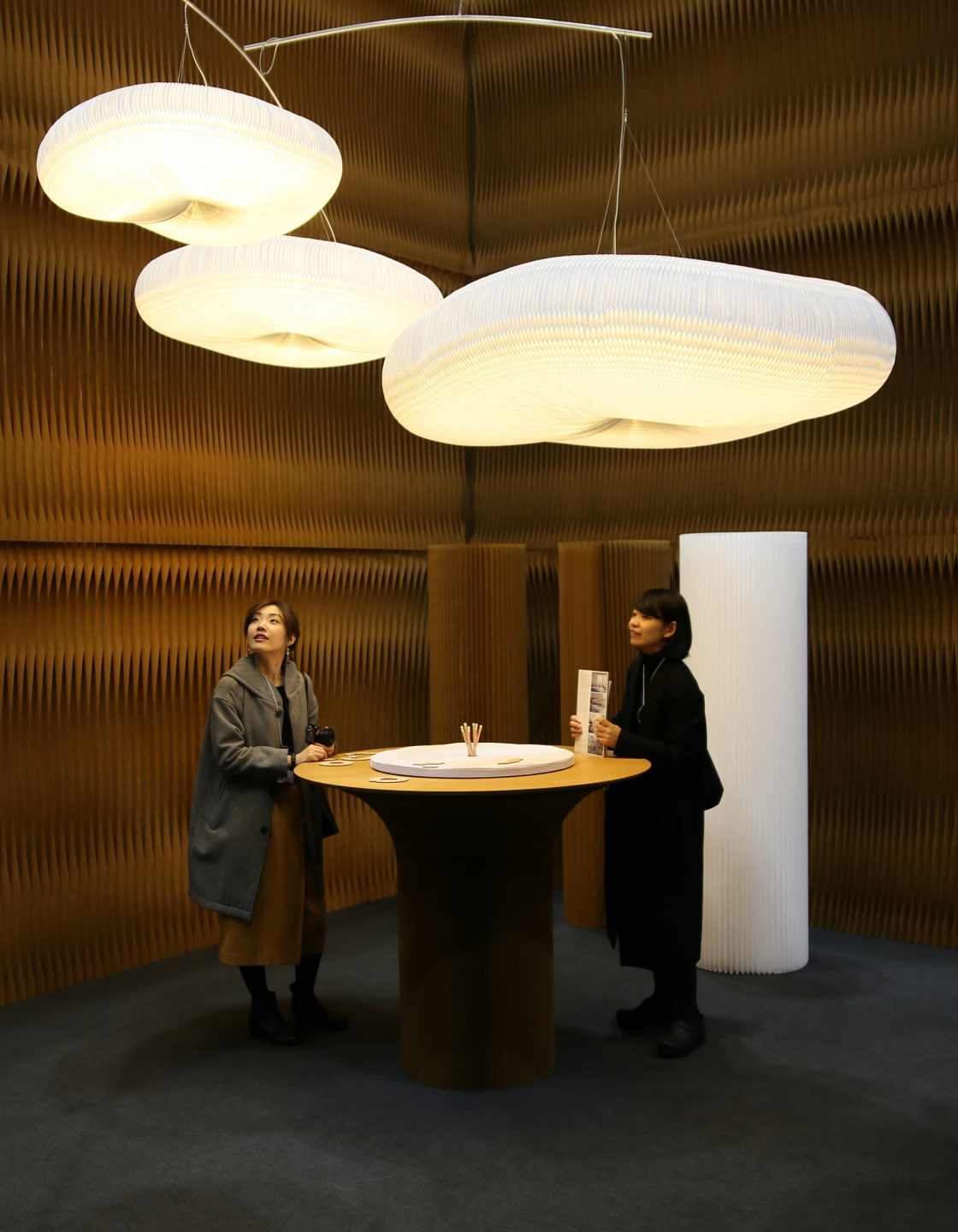 soft lighting cloud mobile by molo - two Japanese guests admire the large cloud mobile at IFFT