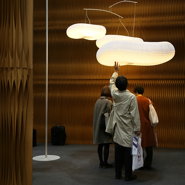 soft lighting cloud mast by molo - a man reaches to touch the textile honeycomb shades of cloud mast at IFFT in Tokyo
