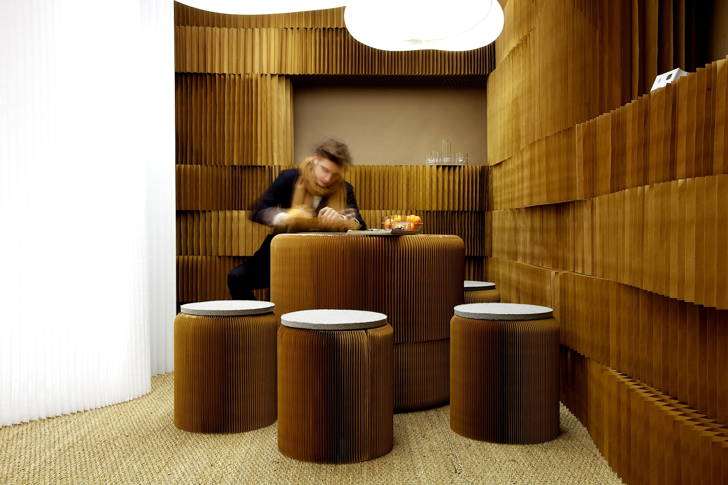 portable paper stool by molo - a man sits at a table made from stacked paper softseating, surrounded by paper softblocks and molo's lighting elements.