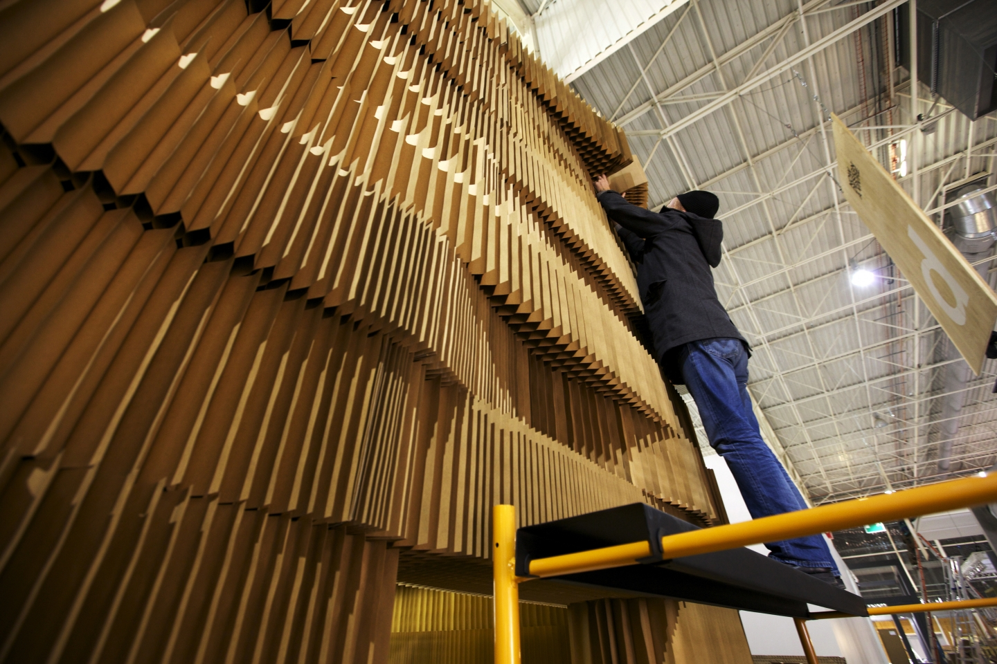 a molo employee stretches to place the highest layer of softblocks for the Maison & Object installation. modular partition wall