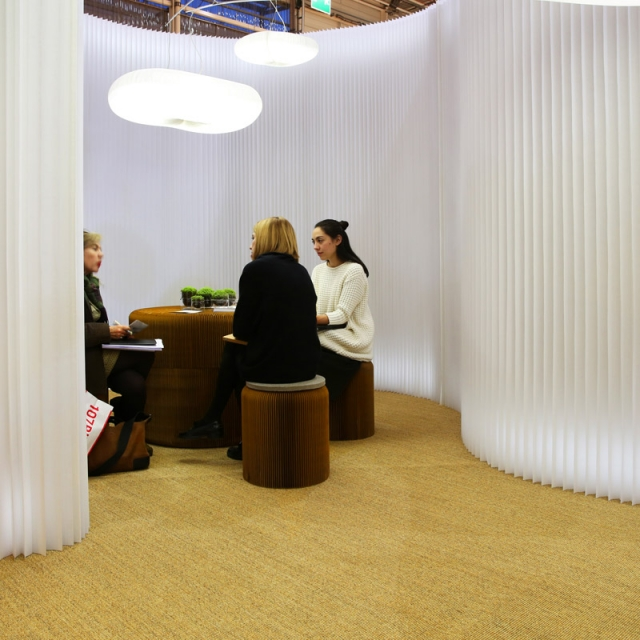 three women have a meeting in a room made from textile softwall and brown paper softseating.