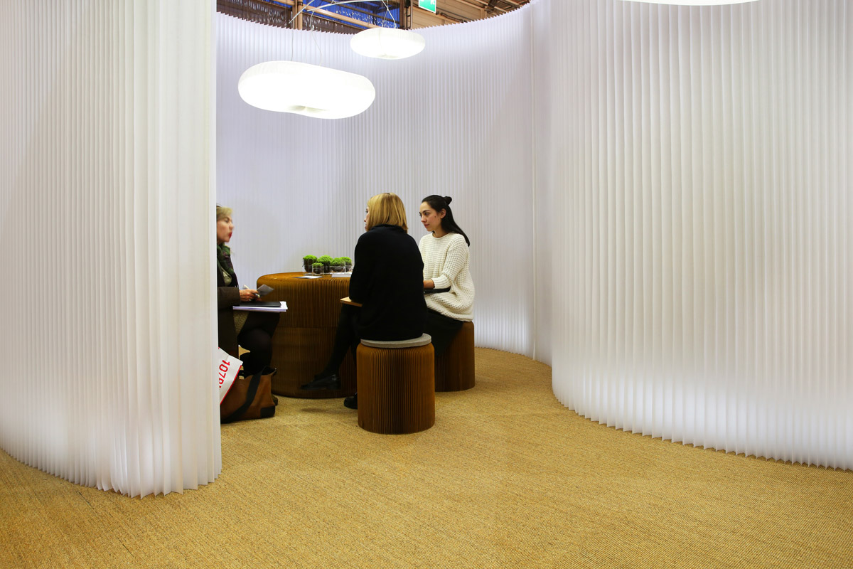 white modular textile wall partitions / cloud acoustic pendant lighting by molo - three women have a meeting in a room made from textile softwall and brown paper softseating.