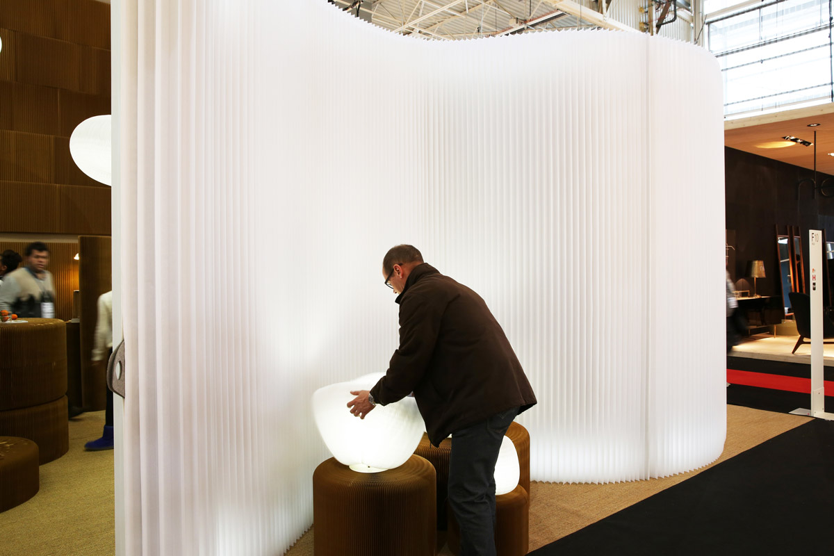 Against a backdrop of a freestanding textile partition wall, a man manipulates urchin softlight's shifting form.