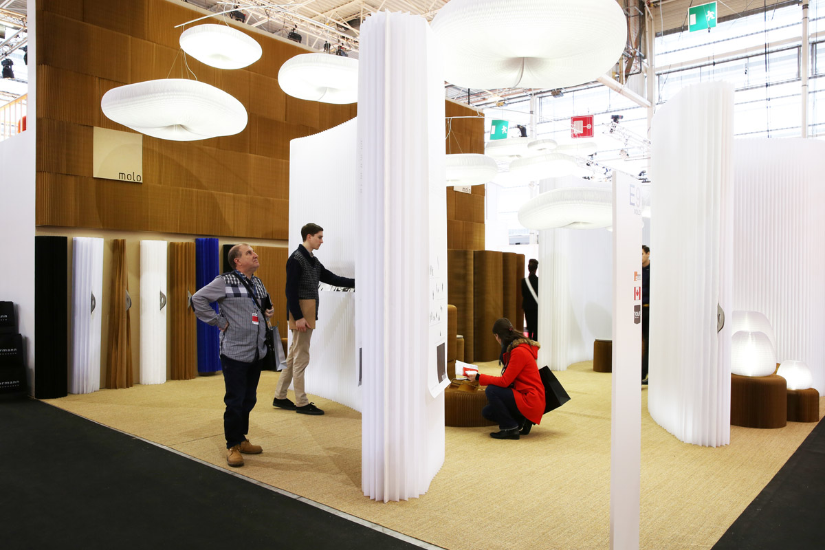 molo's installation at Maison & Objet in 2014 featured cloud softlight mobile, modified textile and softwall + softblock. Three guests explore the products on display.
