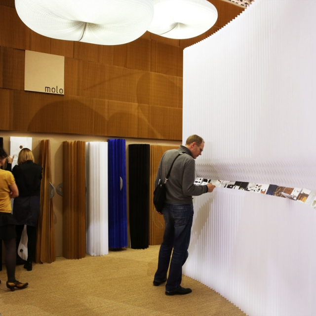 A portion of molo's installation at Maison & Objet 2014. A molo employee demonstrates softwalls to a guest while another visitor examines print materials on display.