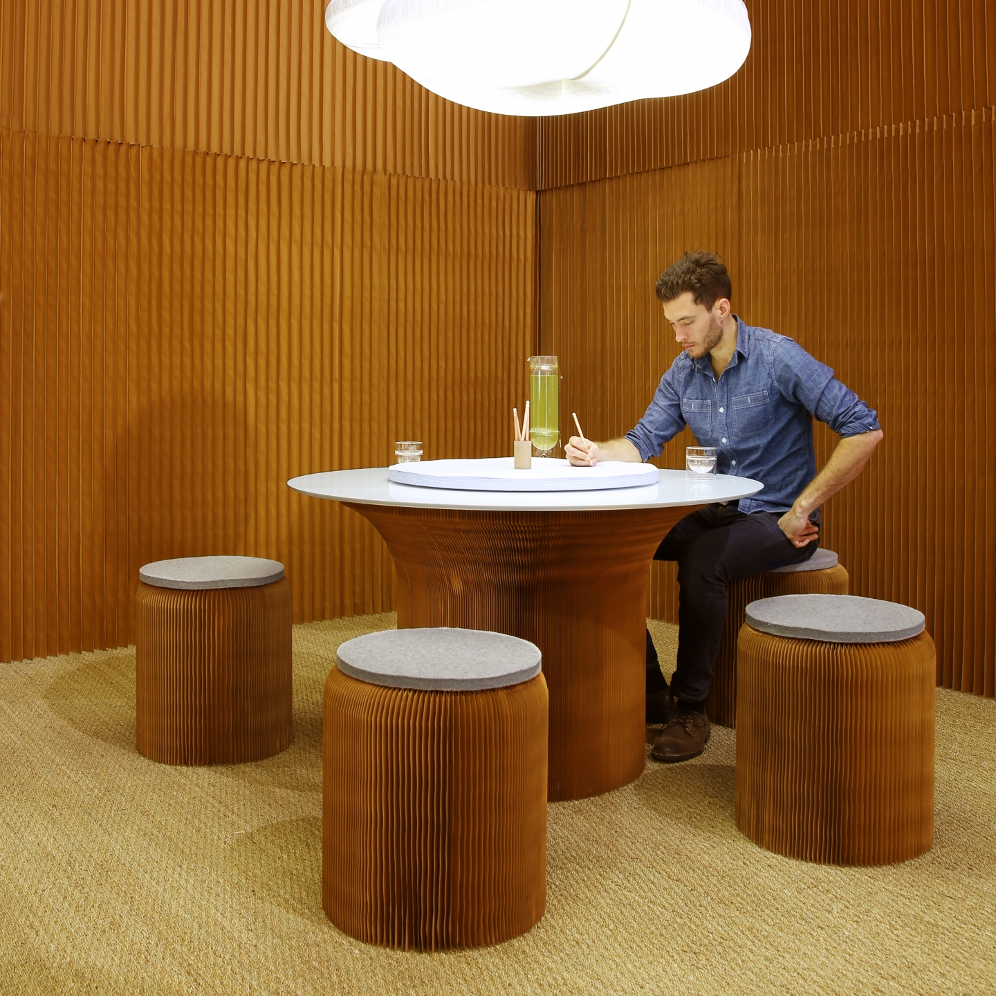 man sits at a cantilever table surrounded by softseating fanning stools