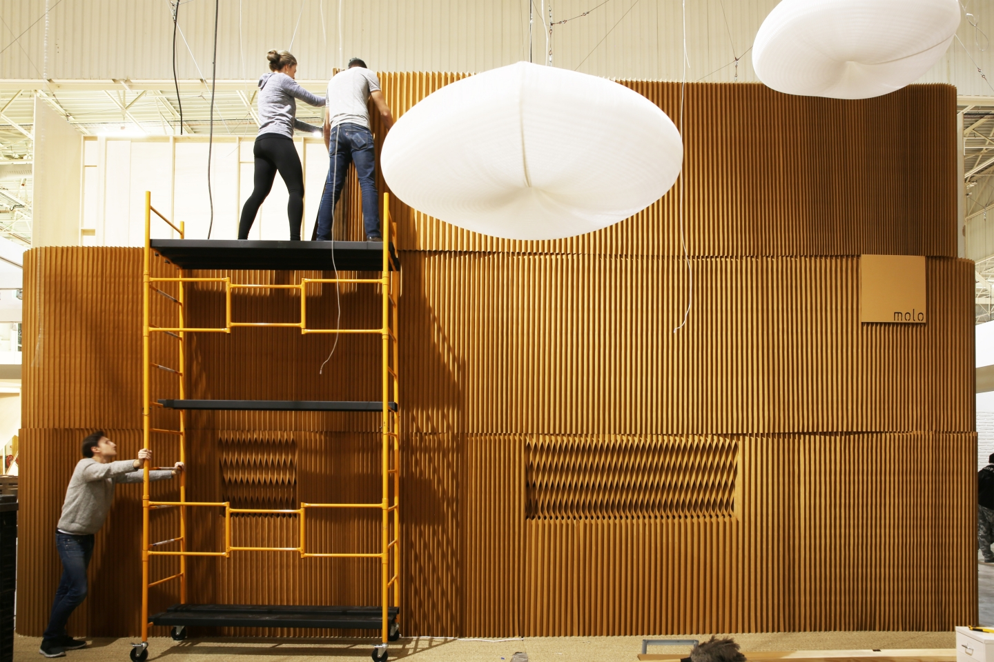two people on cloud lighting and honeycomb paper furniture by molo - a scaffold set up stacks of molo's paper softwall for the Maison & Objet 2015 installation