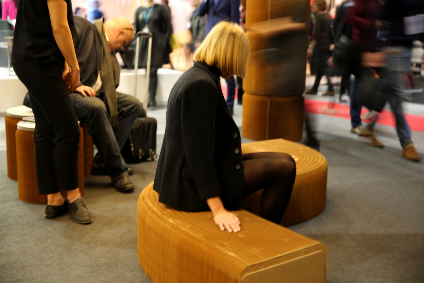 woman sits on a softseating fanning stool + bench at Maison and Objet - modular paper furniture by molo