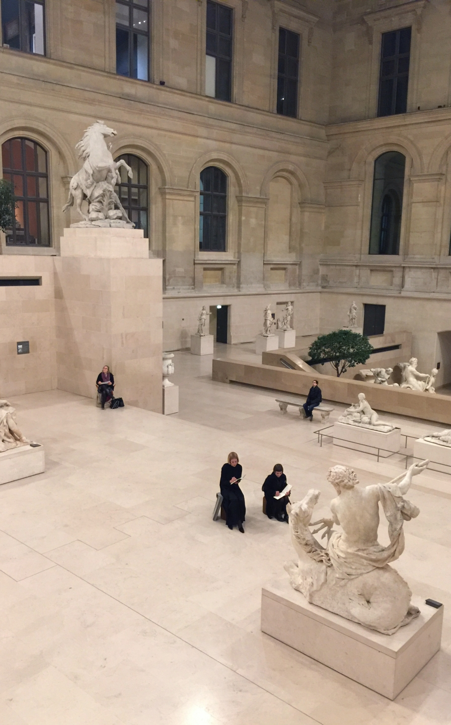 two women use softseating fanning stools as impromptu seats in the sculpture hall at the Louvre
