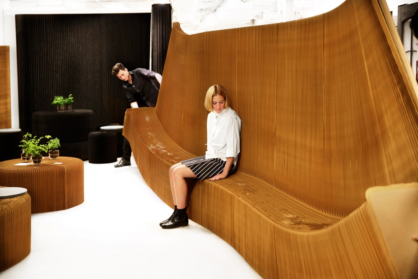 acoustic benchwall partition and paper chair by molo - honeycomb paper furniture - a woman sits on benchwall as the honeycomb geometry is stretched open