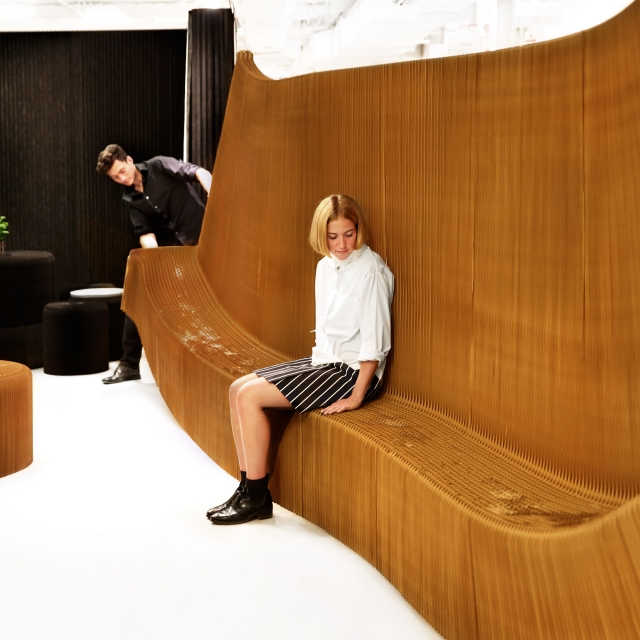 a woman sits on benchwall as the honeycomb geometry is stretched open