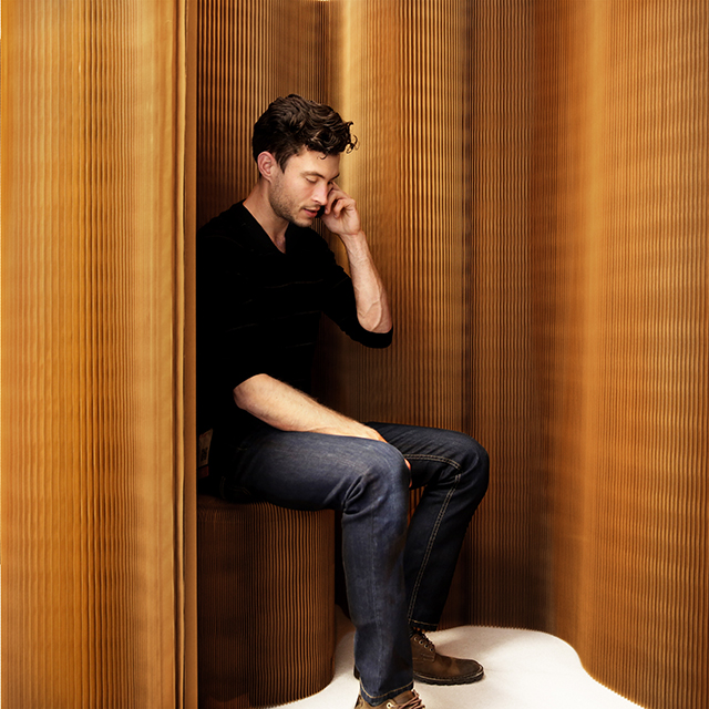 acoustic wall partition and paper chair by molo - a man uses a thinwall nook to have a private phone call