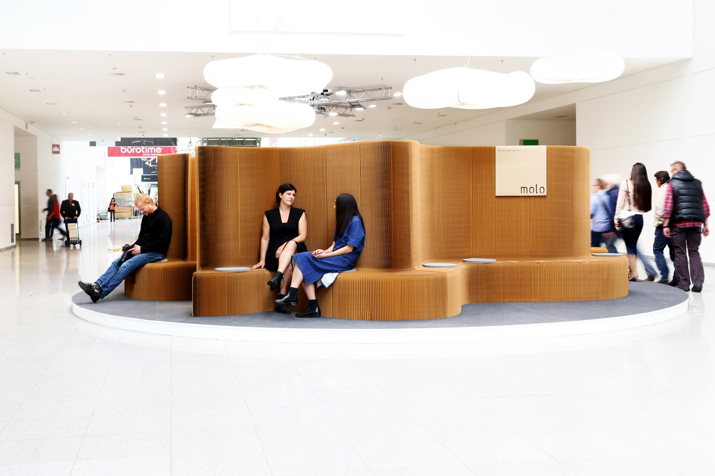 modular paper seating illuminate by its cloud lighting - accordion paper furniture by molo - a series of benchwalls connected by their magnetic end panels and installed at Orgatec 2014