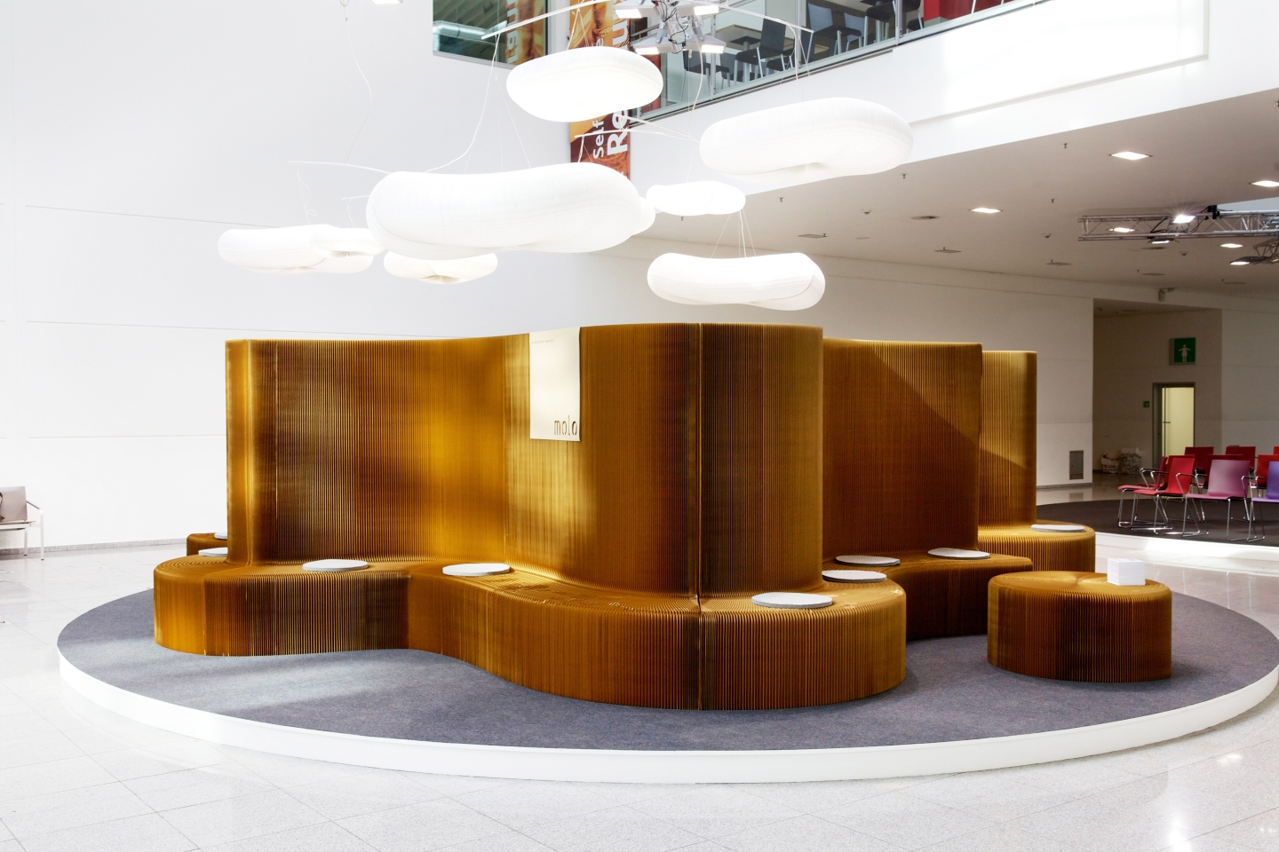 modular paper seating illuminate by its cloud lighting - accordion paper furniture by molo - sunlight glimmers off benchwall's pleated structure