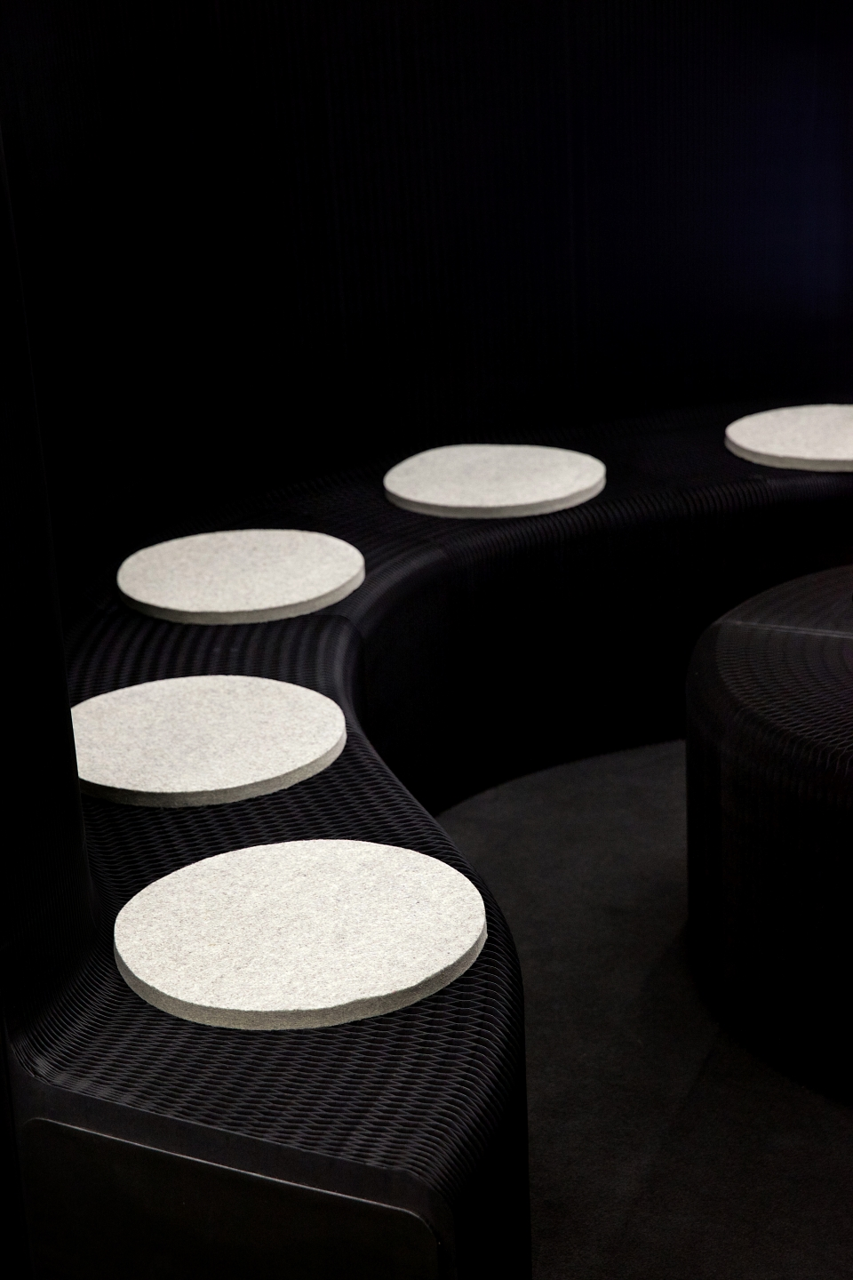 grey wool felt pads line a black benchwall at Orgatec 2014