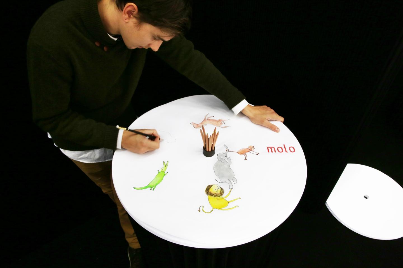 a man doodles cartoons on molo's sketching circles accessory