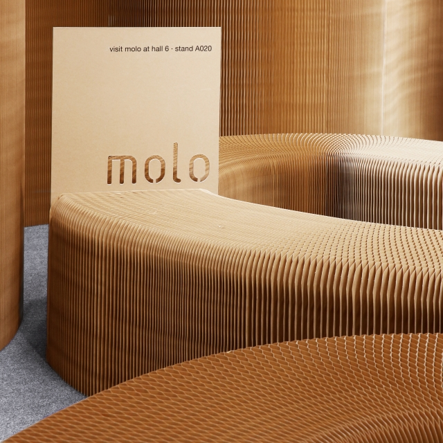 displaying promotional materials with molo; a sign is sandwiched between the magnetic end panels of two paper benches.