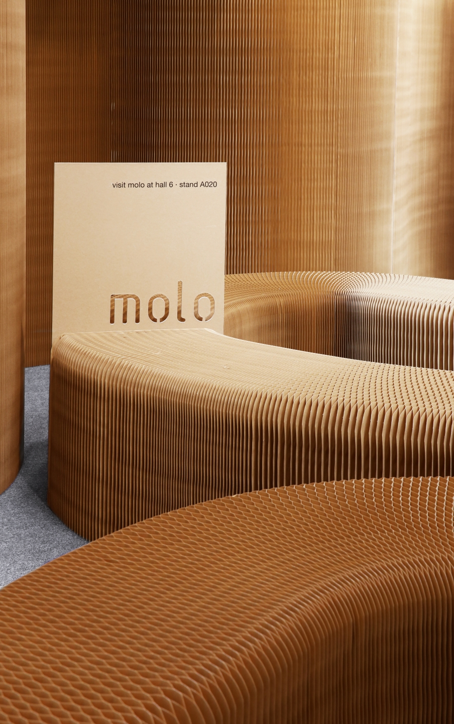 paper bench and modular wall partitions by molo - displaying promotional materials with molo; a sign is sandwiched between the magnetic end panels of two paper benches.