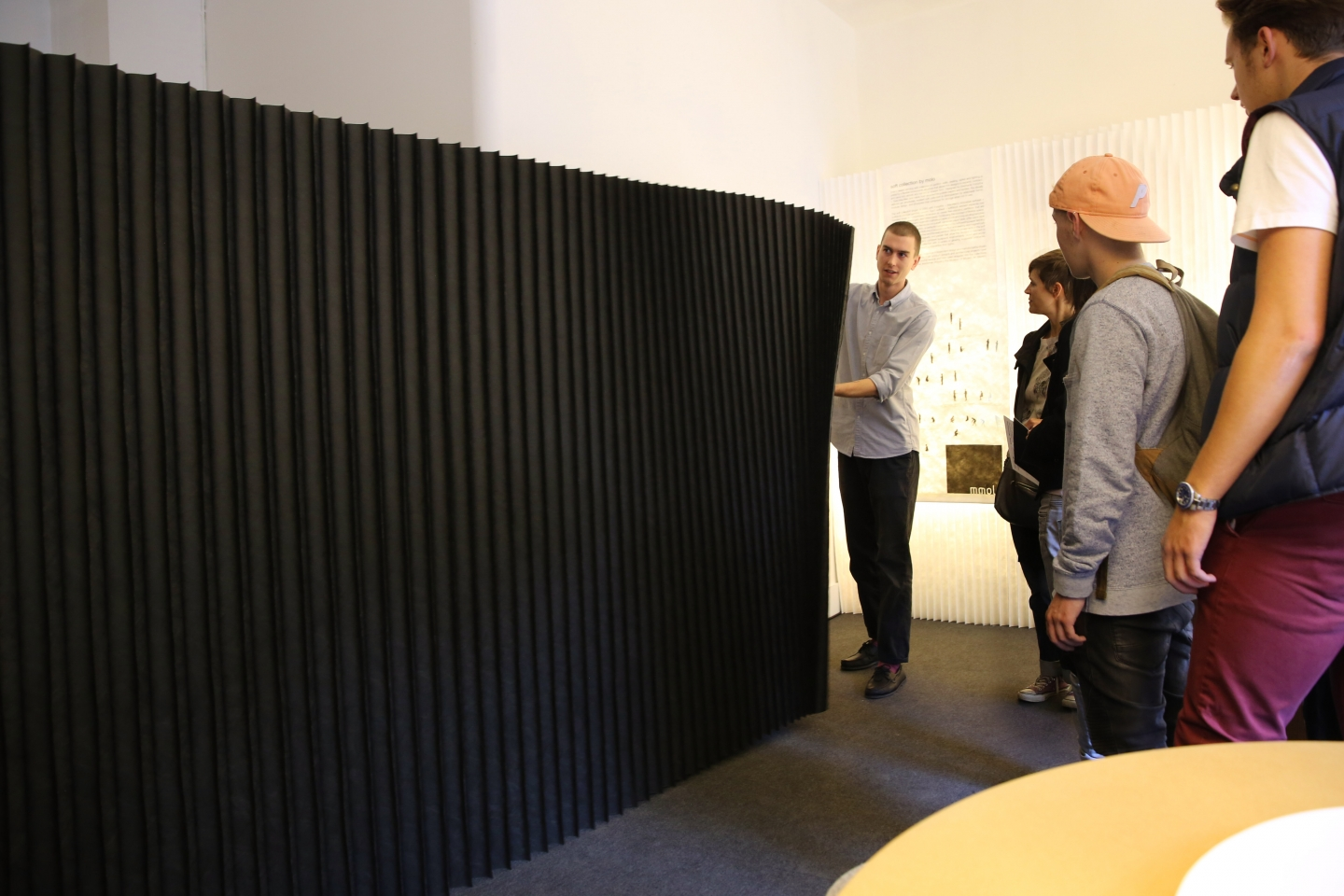 stretching open a softwall at Design Junction London - paper / textile acoustic wall partition in black by molo