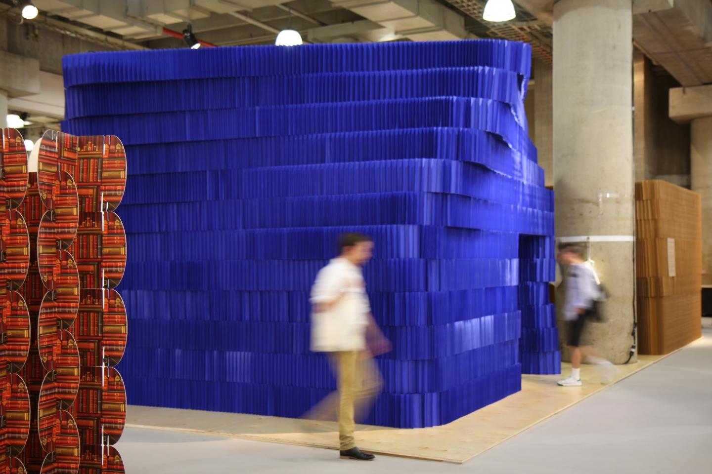 blurred figure strolls past the indigo softblock installation at icff - indigo paper softblock / modular room divider - indigo paper softblock / modular room divider
