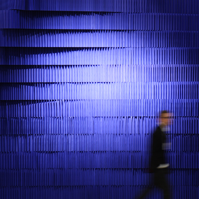 figure silhouetted against a room stacked from indigo softblocks - indigo paper softblock / modular room divider