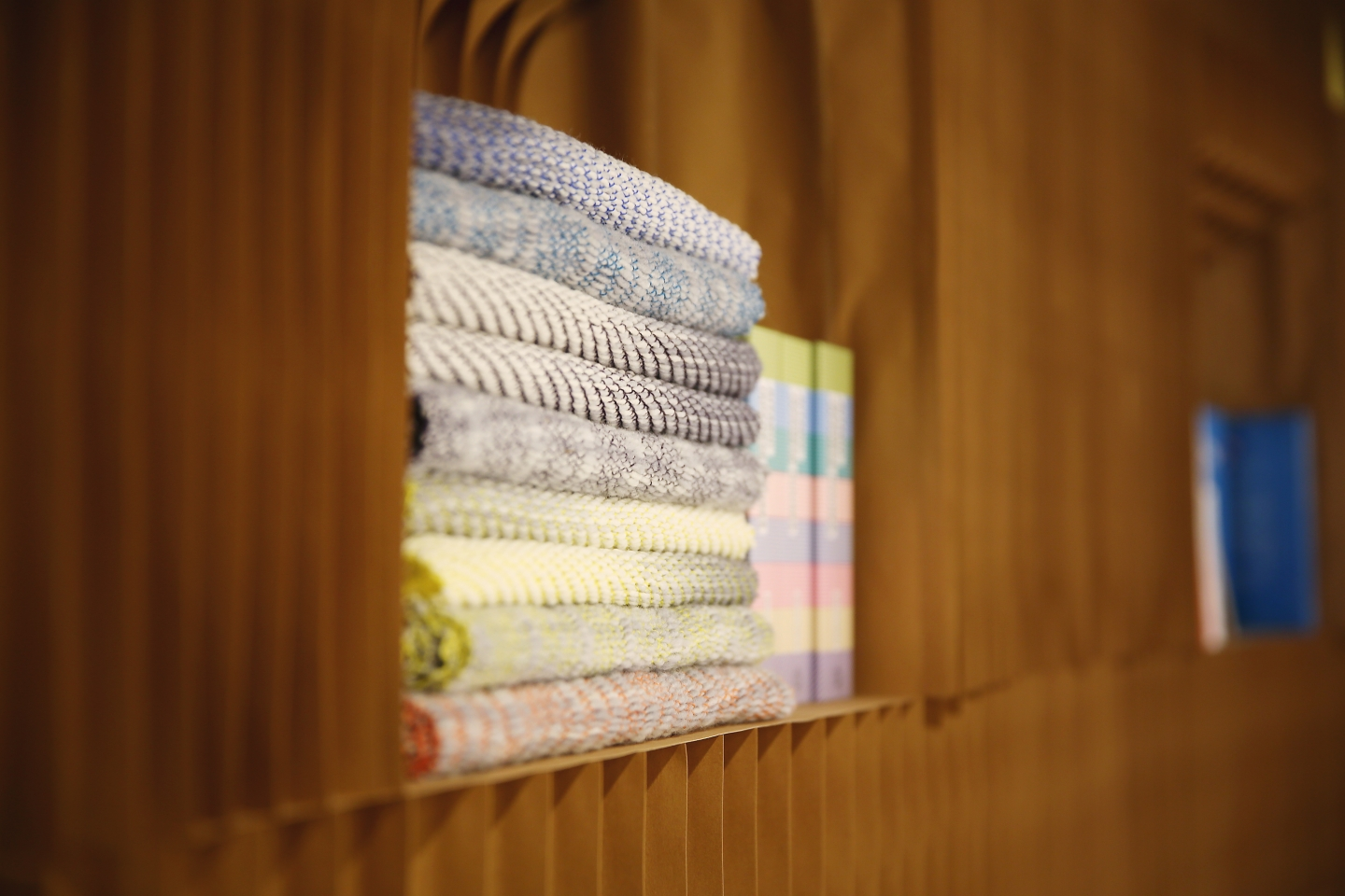 expandable paper furniture by molo - a stack of fabric and books fit into a nook made from a space in paper softblocks