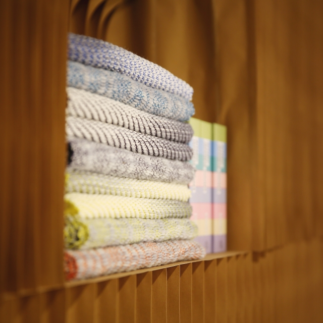 a stack of fabric and books fit into a nook made from a space in paper softblocks