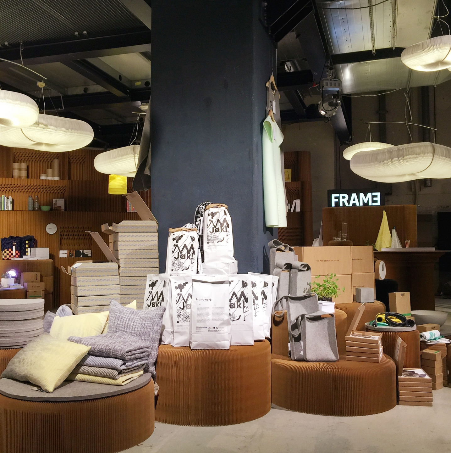expandable paper seating and furniture by molo - molo's various table and seating elements easily double as surfaces for product display, as in this booth for FRAME Magazine