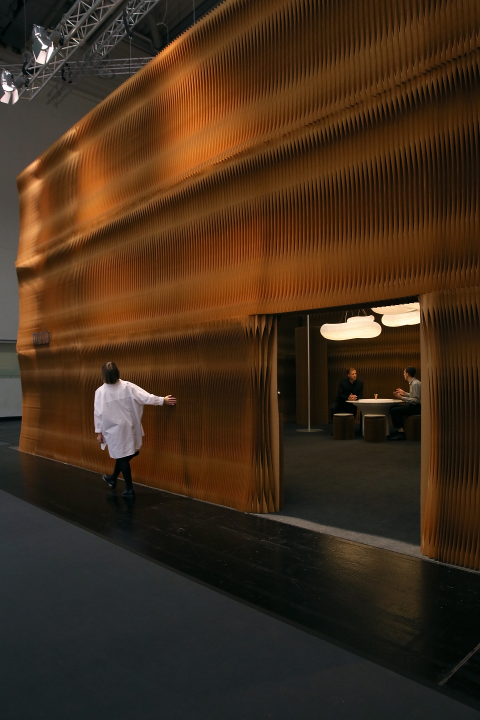 paper accordion wall partitions by molo - a woman runs her fingers along the scalloped pleats of a custom-cut softwall