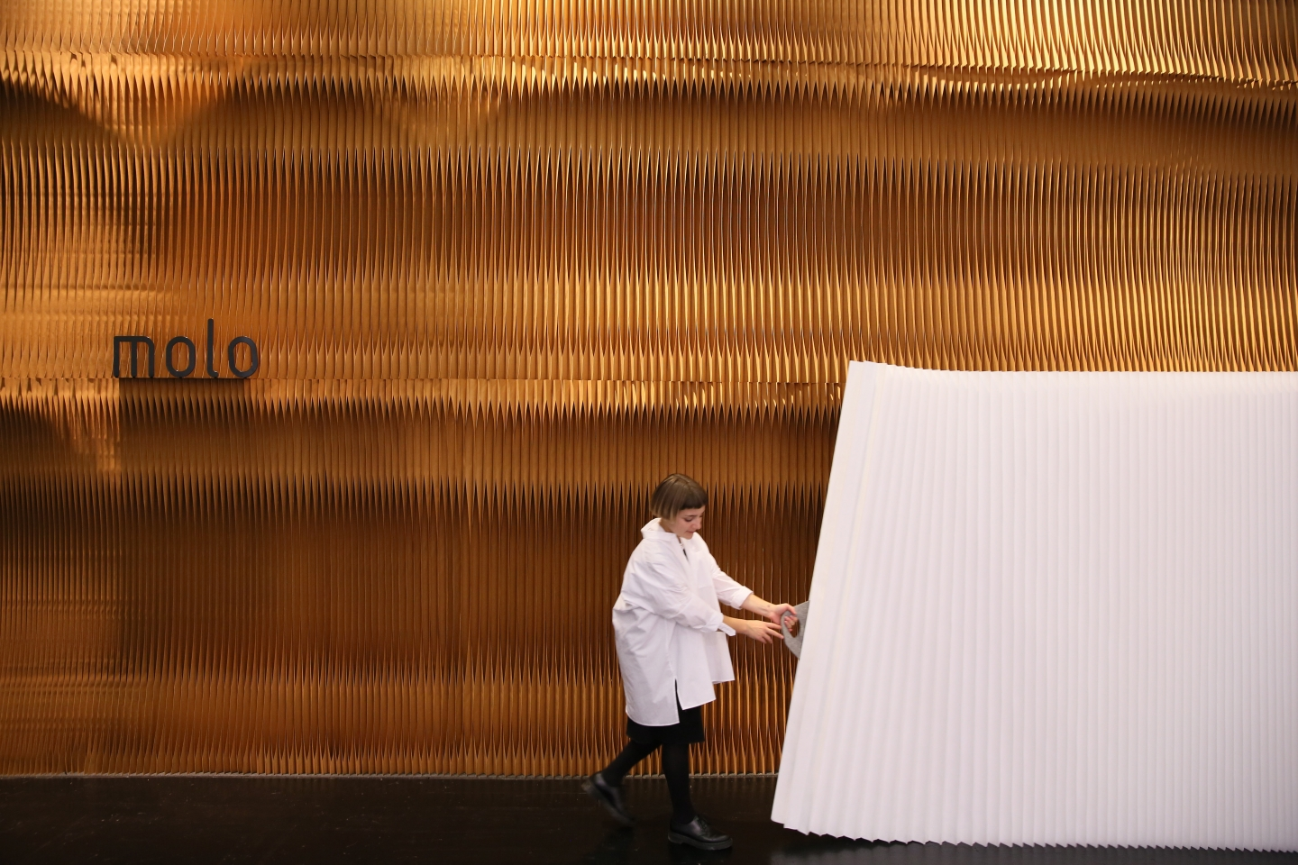 white accordion wall partition by molo - a woman pulls open a textile softwall at Orgatec 2016