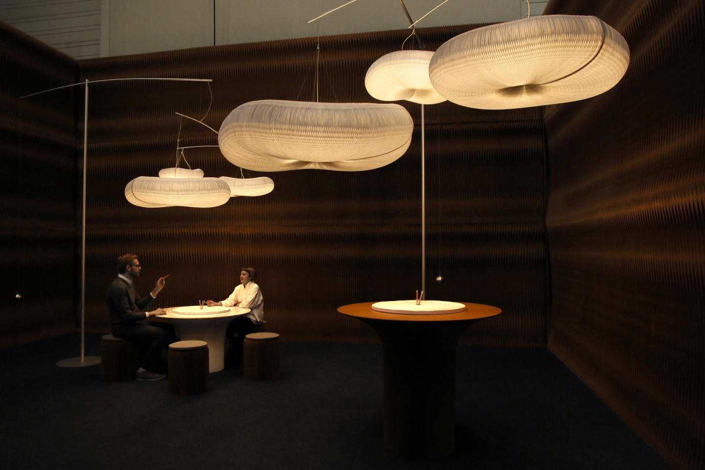 paper accordion seating, furniture and lighting by molo - two people work at a cantilever table under a sky of cloud softlight