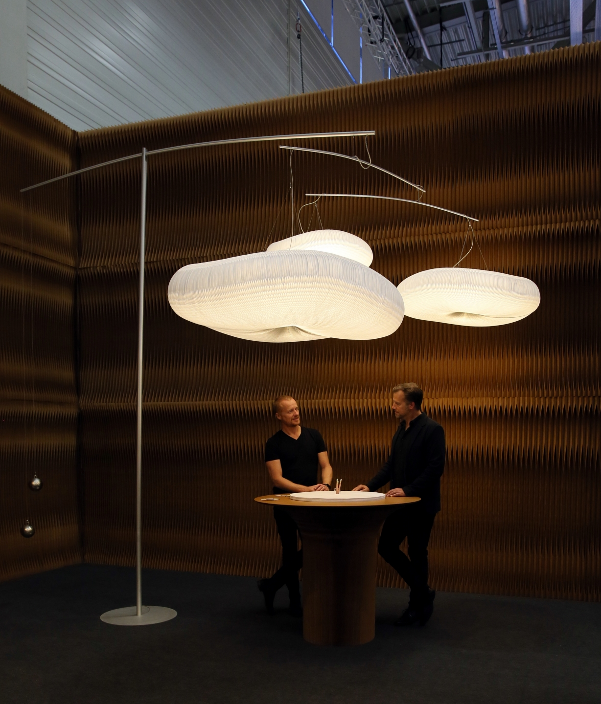 soft lighting and paper furniture by molo - two men share a conversation in molo's booth at Orgatec 2016