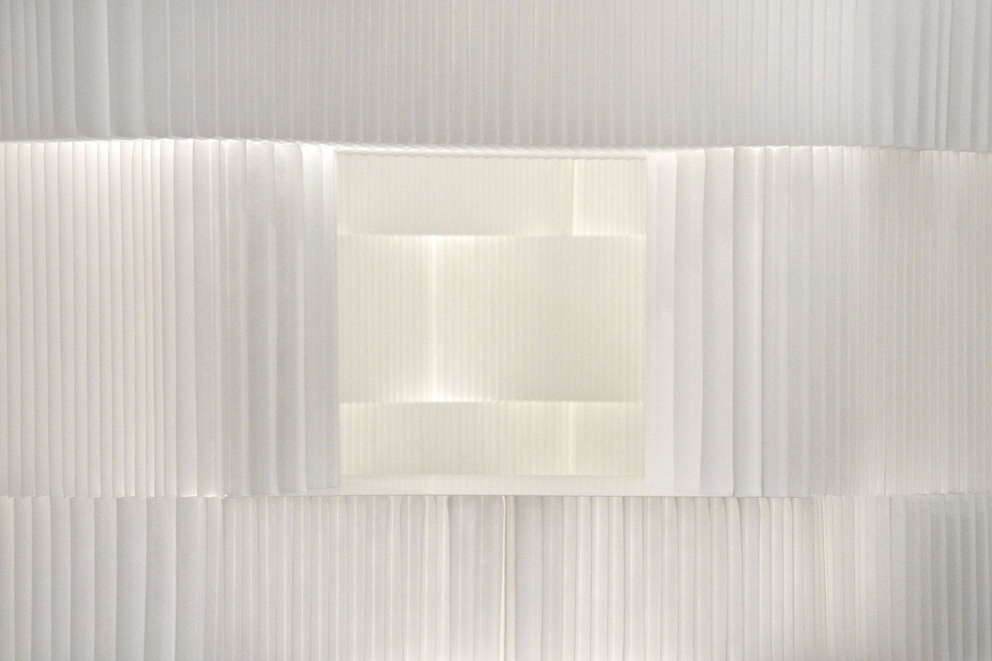 Light shines through the delicate pleats of textile softblock.