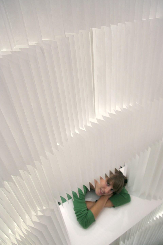 A woman peeks through a window made from textile softblocks / modular room divider.