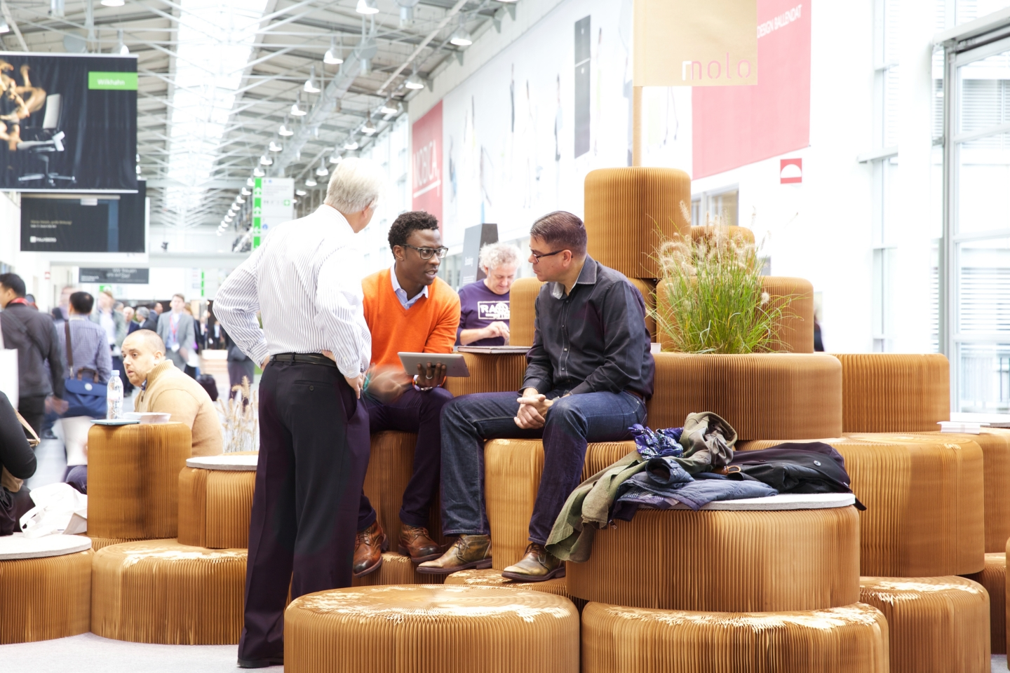 modular paper furniture by molo - Three visitors to Orgatec 2014 discuss business while taking a rest on a hill made of stacked softseating fanning stools.