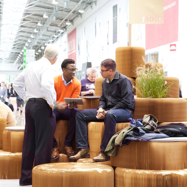 Three visitors to Orgatec 2014 discuss business while taking a rest on a hill made of stacked softseating fanning stools.