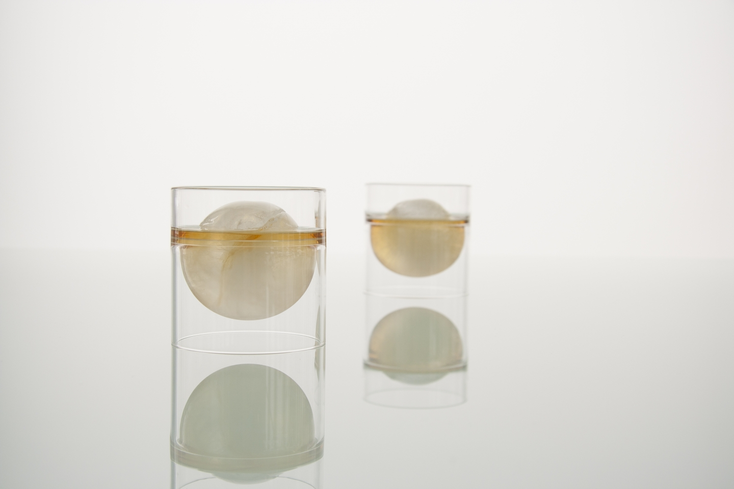 Two float tea cups filled with whiskey an Japanese ice balls.